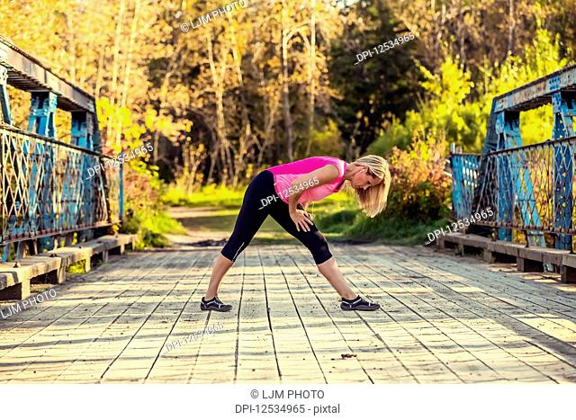An attractive middle-aged woman listens to music on her smart phone and pauses to stretch on a bridge during a run on a beautiful warm fall evening in a city...