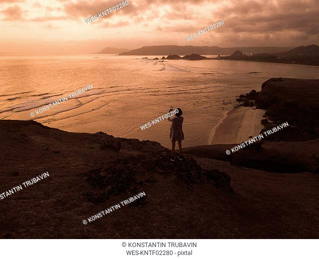 Indonesia, Lombok, young woman at coast at sunset