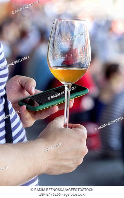 Woman holding a glass of wine and writes sms on phone