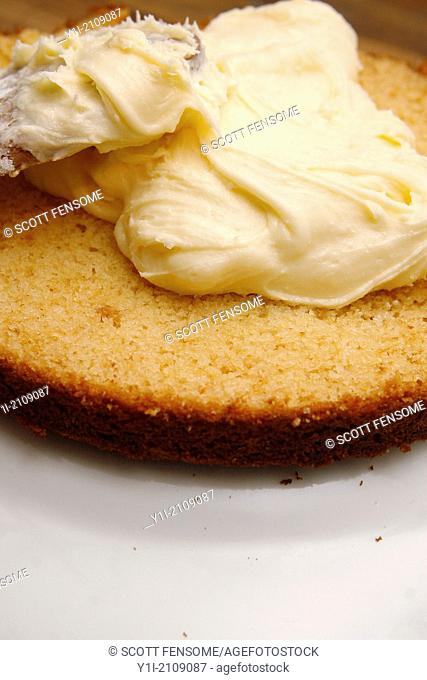 buttercream being spread on lemon curd cake