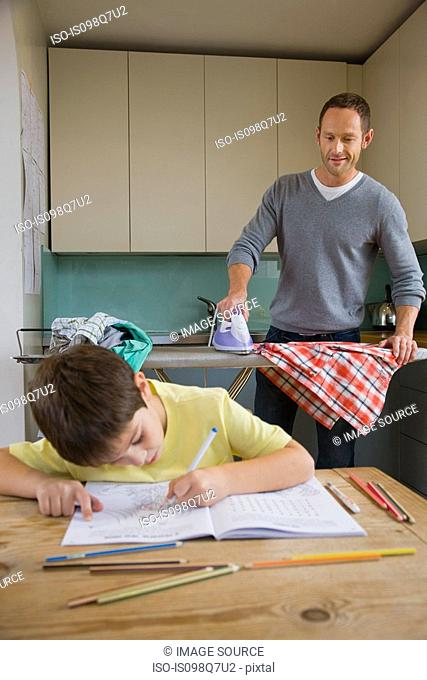 Father ironing and son colouring in