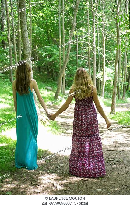 Female friends walking hand in hand on path through woods