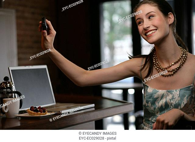 Young happy woman holding up phone at cafe