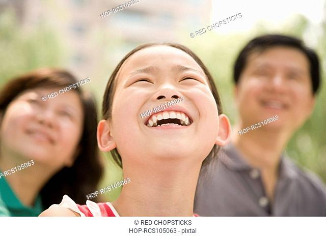 Close-up of a girl smiling with her parents in the background