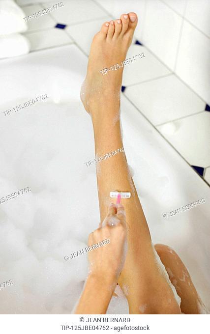 Woman having bath and shaving legs