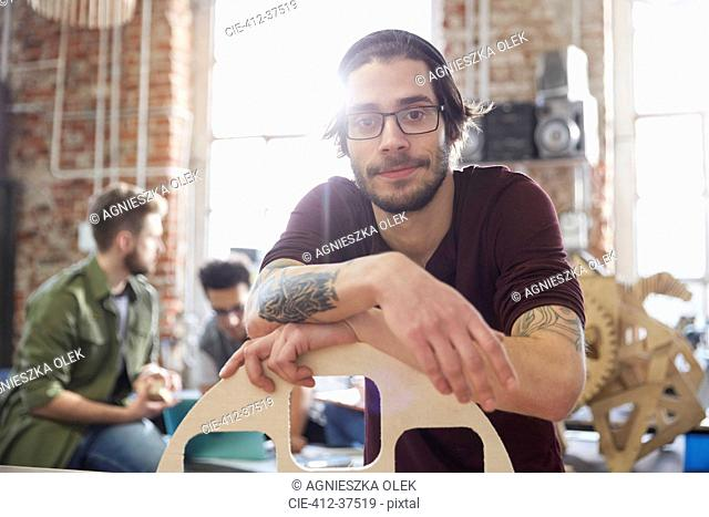 Portrait confident male designer with tattoos leaning on prototype in workshop