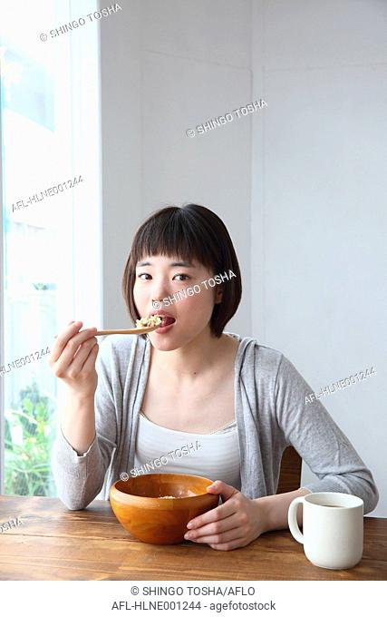 Young Japanese woman having breakfast in airy room