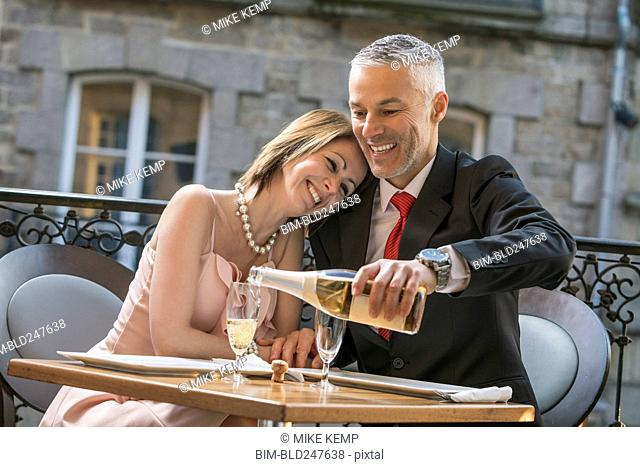 Well-dressed Caucasian man pouring champagne for woman