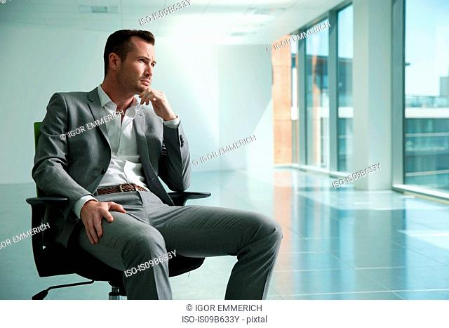 Businessman sitting in chair in empty office space, thoughtful expression