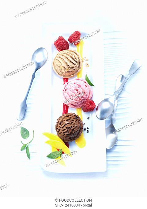 Various ice cream scoops with mango and raspberry sauce