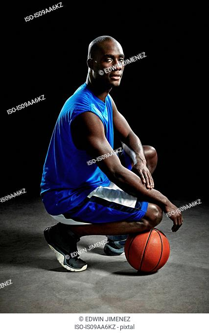 Studio portrait of basketball player kneeling on ball