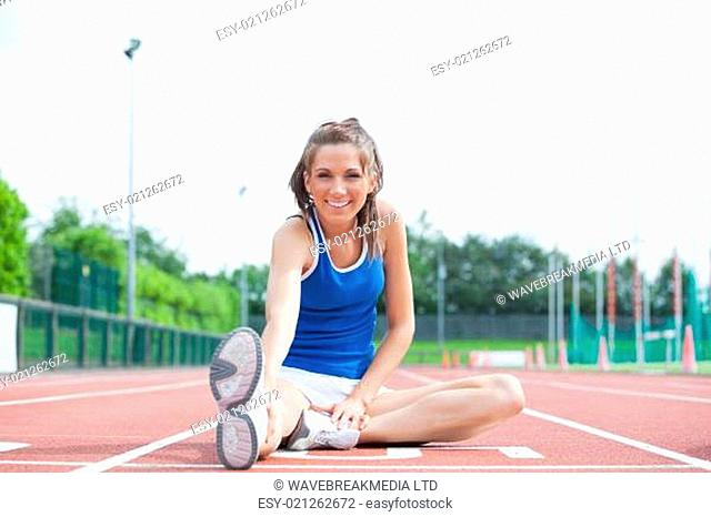 Cheerful woman stretching her leg on a track