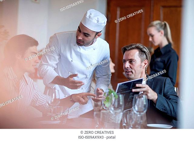 Chef chatting with customers in restaurant
