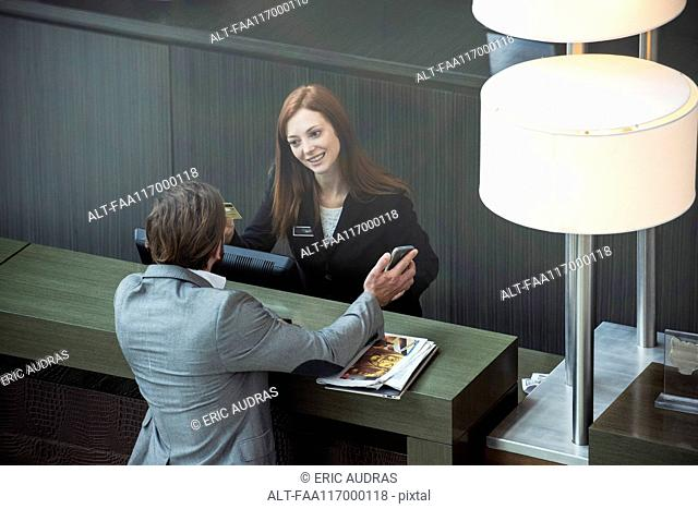 Businessman showing smart phone to female receptionist