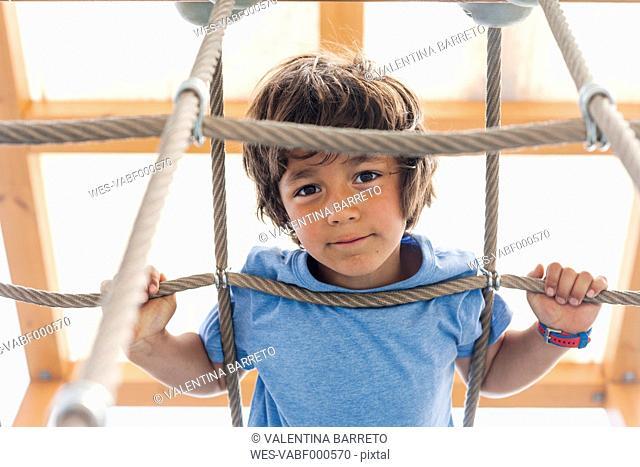 Portrait of little boy on hanging bridge of a playground