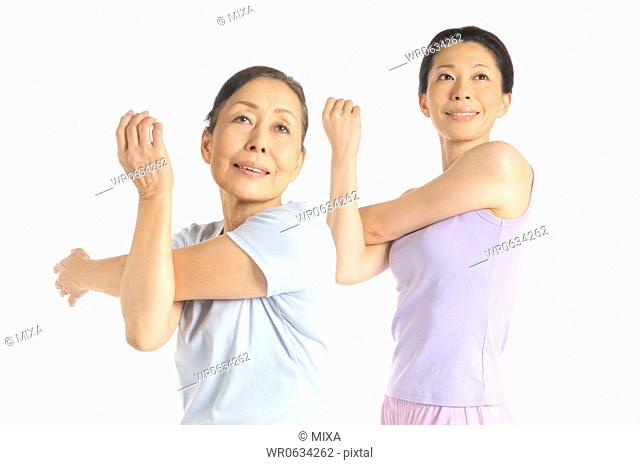 Senior woman and mid adult woman stretching upper arms