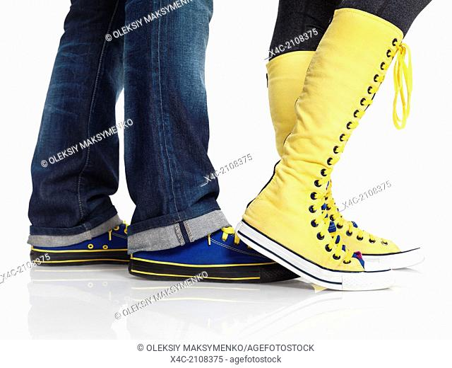 Closeup of woman and man legs in colorful blue and yellow trainers shoes isolated on white background