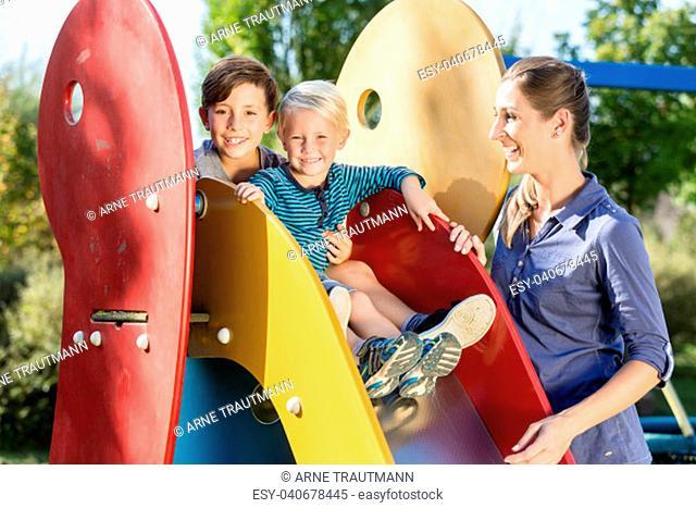 Happy family playing on adventure playground, children chuting chute