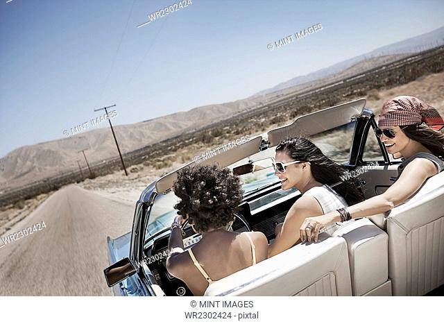 Three young people in a pale blue convertible car, driving on the open road across a flat dry plain
