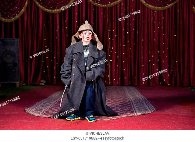 Talented boy standing and holding a sword while wearing oversized retro gray coat and Russian hat over modern casual clothes during theatrical play on stage