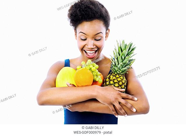 Portrait of excited young woman holding fruits in her arm in front of white background