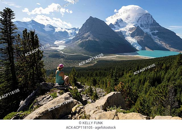 A young woman rest and checks out the view on the Mumm Basis trail with Mt. Robson and Rearguard mountain in the background, Mt
