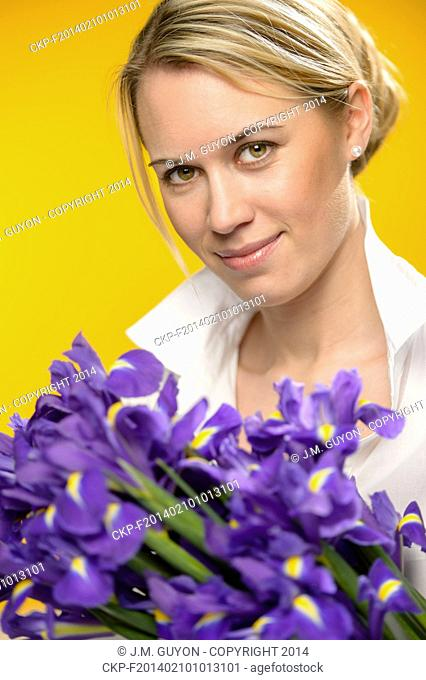 Woman with spring flowers purple iris on yellow background