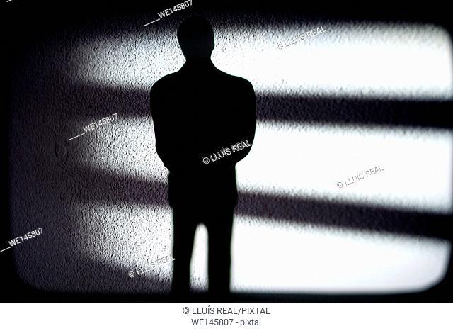 silueta de un hombre irreconocible y de incognito sobre unas sombras, silhouette of a unrecognizable and incognito man
