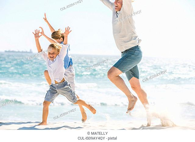 Father and children jumping on beach