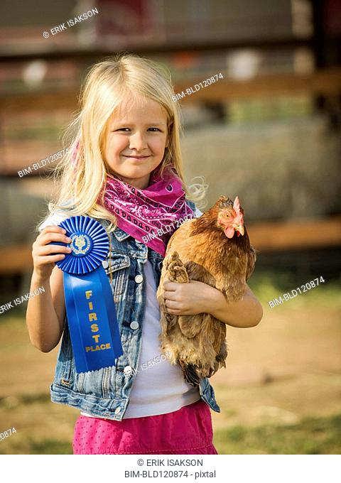 Caucasian girl with prize winning chicken on farm