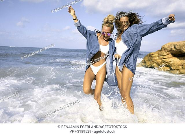 Two women walking in sea water at beach, Chersonissos, Crete, Greece