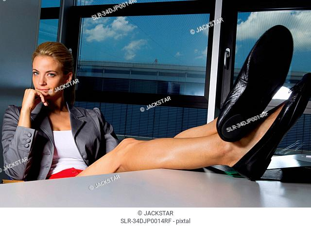 Businesswoman resting feet on desk
