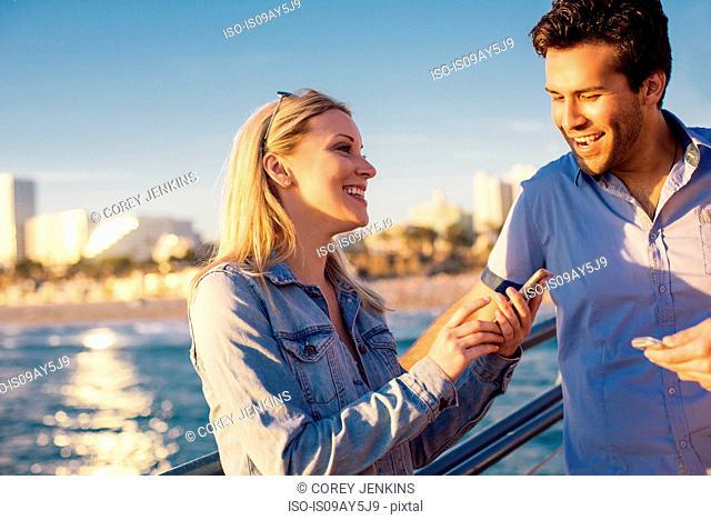 Young couple reading smartphone text on pier, Santa Monica, California, USA