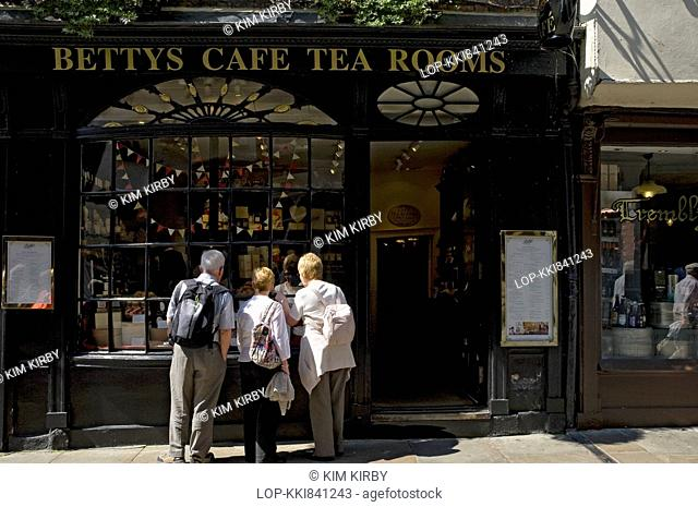 People looking in the window of Little Bettys cafe and tea rooms in Stonegate