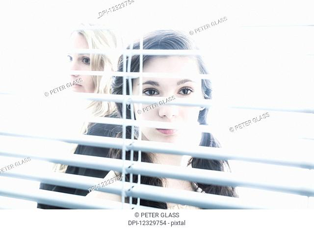 Teenage Girl And Young Blond Woman Looking Through The Blinds On A Window; Connecticut, United States Of America