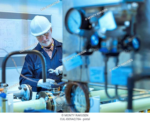 Senior engineer working on pipework in power station