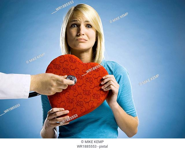 woman holding a heart with a stethoscope against it