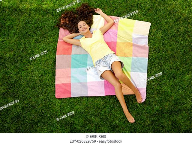 Happy young woman sitting on a blanket with arms stretched