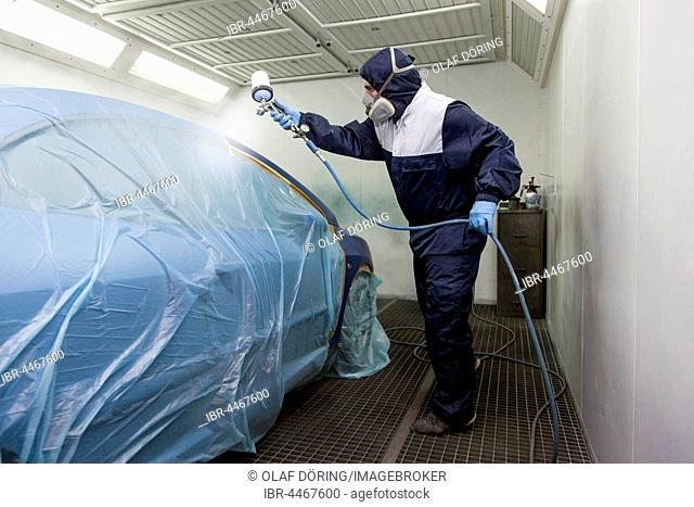 Vehicle painter during a partial painting of a car in the spray booth, Düsseldorf, North Rhine-Westphalia, Germany