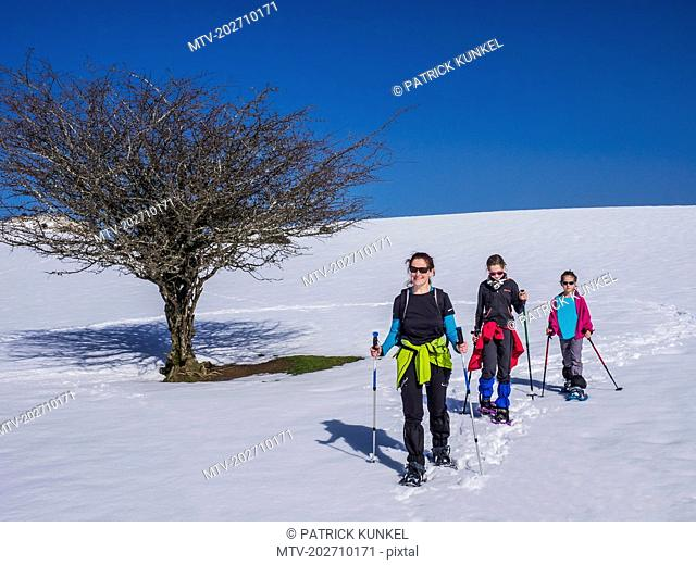 Mother with daughters hiking on snow slope