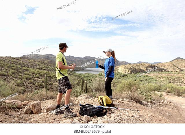Couple resting while hiking in desert