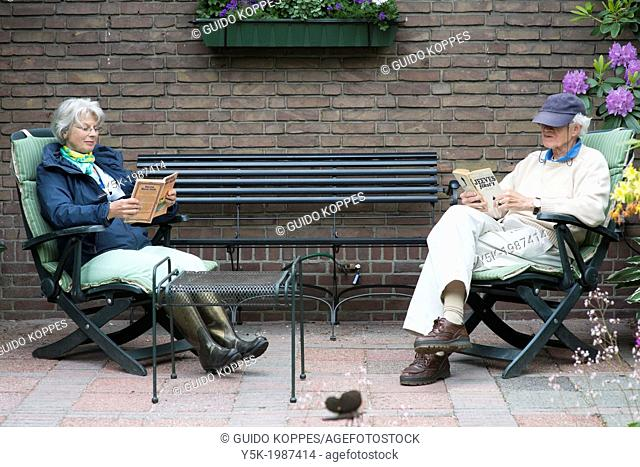 Hilligersberg, Rotterdam, Netherlands. Older couple, together reading a book, in their garden behind their house