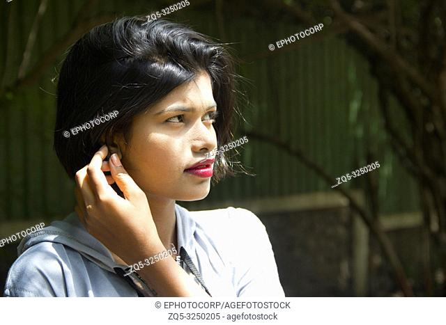 Young Indian girl with short hair with her hand near ear looking away and posing for camera in a sunlight, Pune