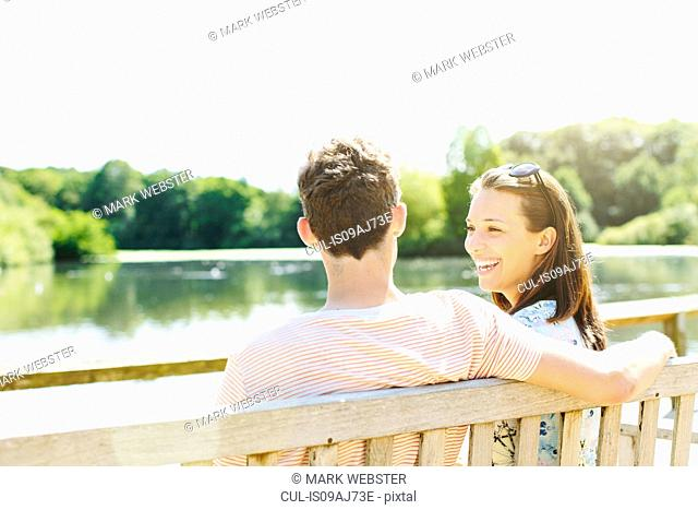 Couple sitting on wooden park bench
