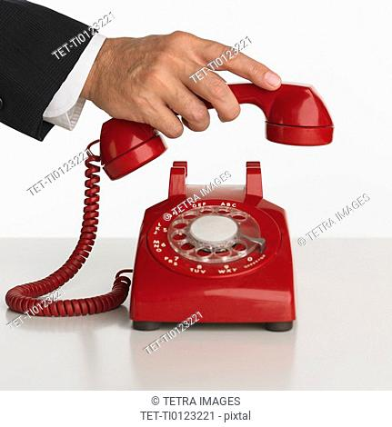 Close up studio shot of man picking up rotary telephone