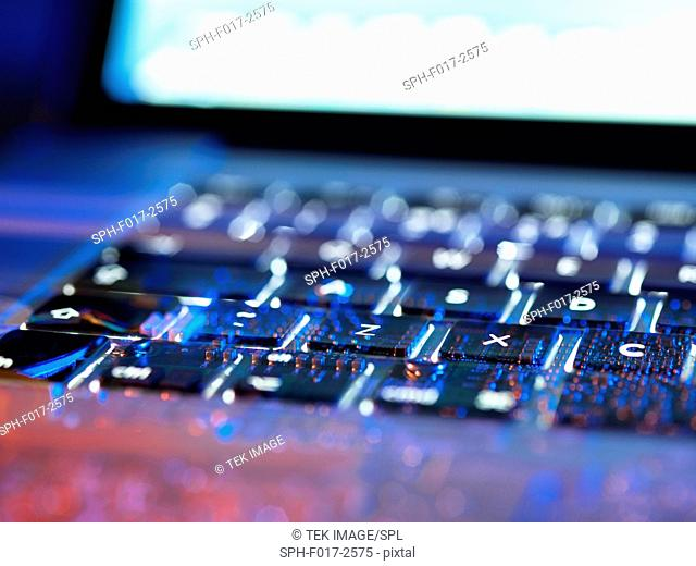 Double exposure of a laptop computer keyboard exposing the electronics underneath