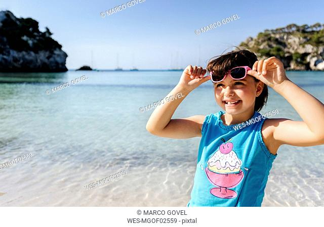 Portrait of smiling little girl standing in front of the sea