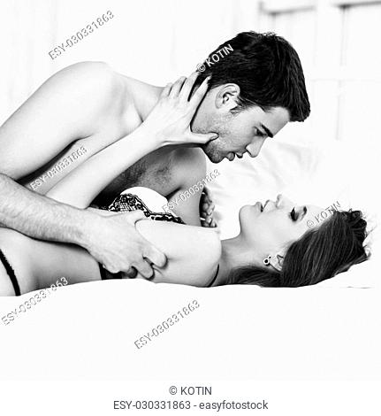 Young passionate couple making love in bed at home