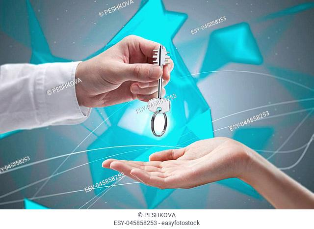sales purchase, buying, renting and selling concept with one hand giving key to another on abstract geometric background
