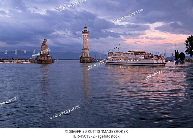 Illuminated excursion boat in the harbor with lighthouse, evening mood, Lindau, Lake Constance, Bavaria, Germany